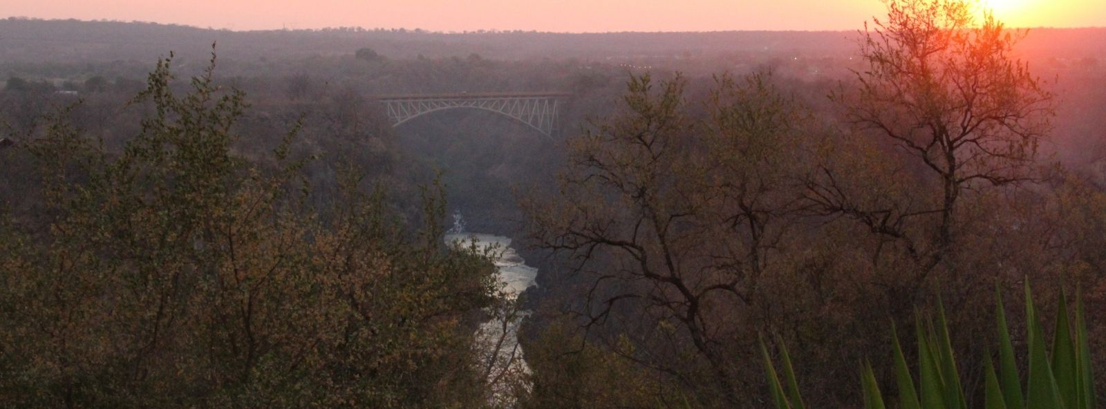 Photo at Sunset of the Victoria Falls Bridge from a distance with Zambezi river flowing below