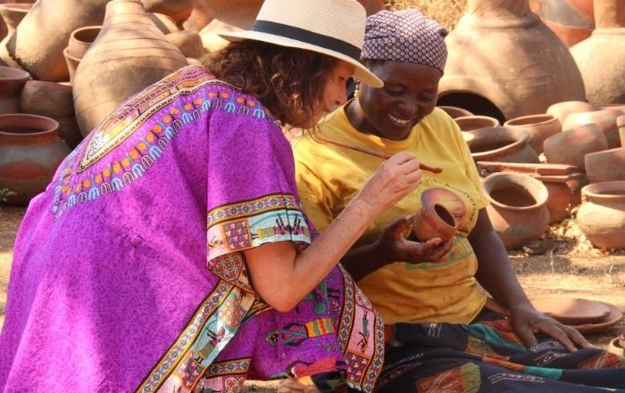 Alexandra's Africa guest kneeling next to Venda lady, all in bright clothes, being taught how to paint a Venda clay pot