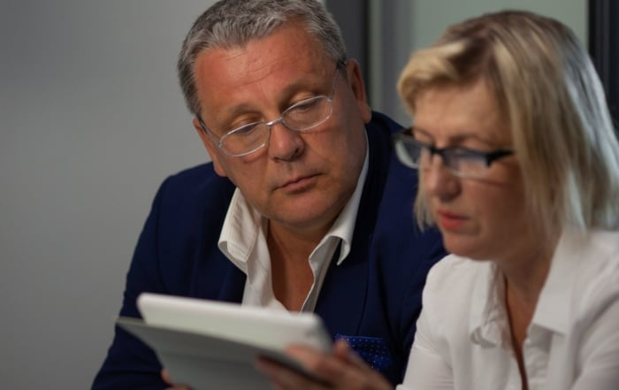 two adults working together on an iPad